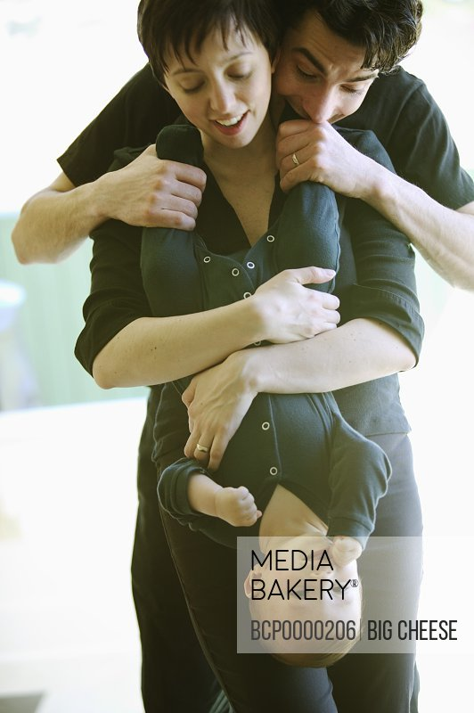 A father and mother holding their baby upside down.