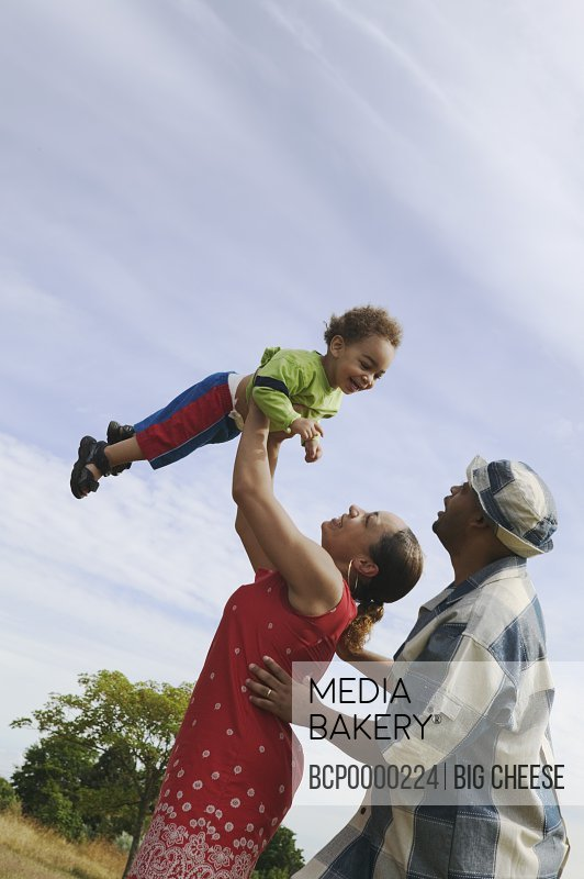 Couple lifting their small son in the air.