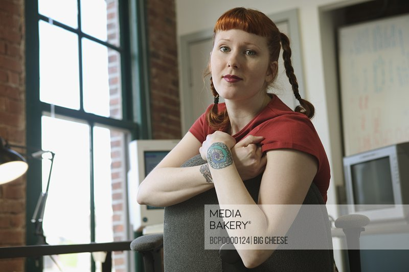 Portrait of a red-haired woman in her office.