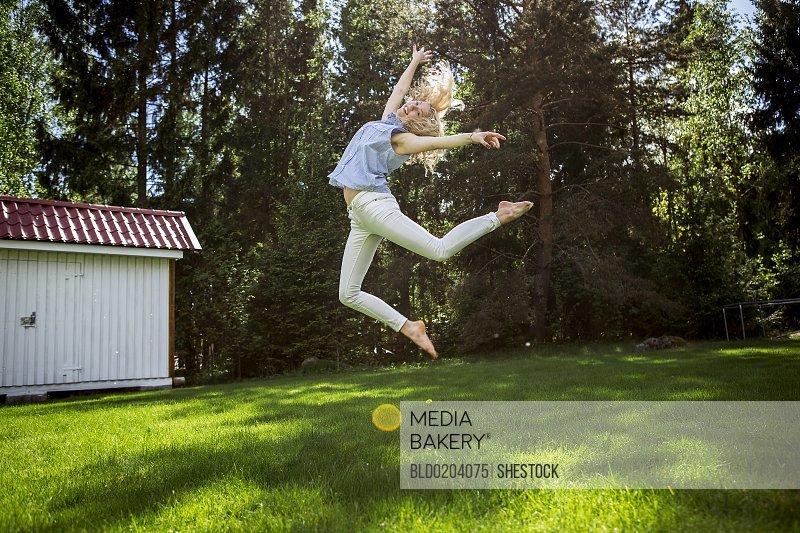 Woman jumping for joy in backyard