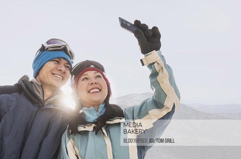 Couple in winter clothing taking selfie near mountain