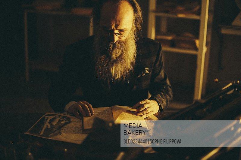Caucasian man with beard reading book