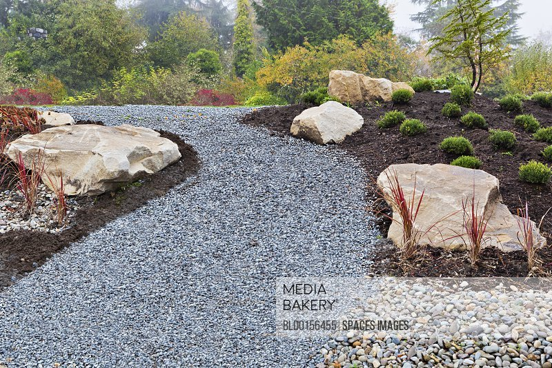 Gravel path and rocks in landscaped garden
