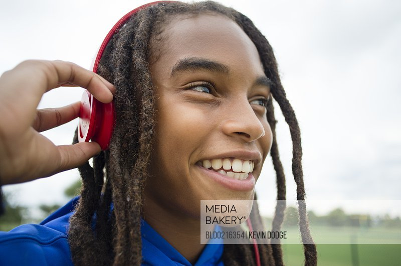 Mixed race boy listening to headphones outdoors
