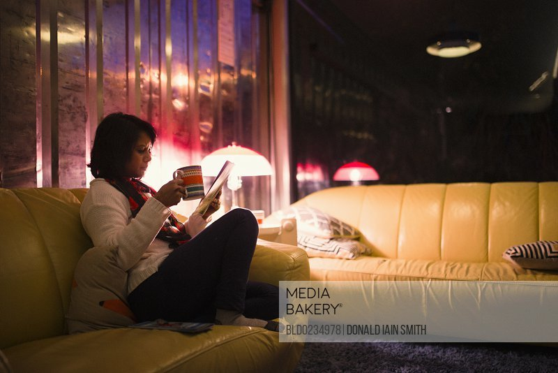 Woman drinking tea and reading magazine on sofa