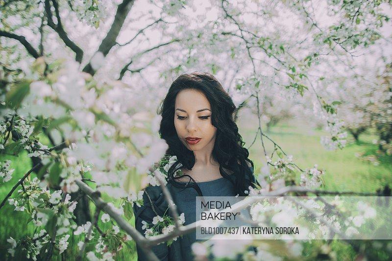 Caucasian woman standing near flowering tree