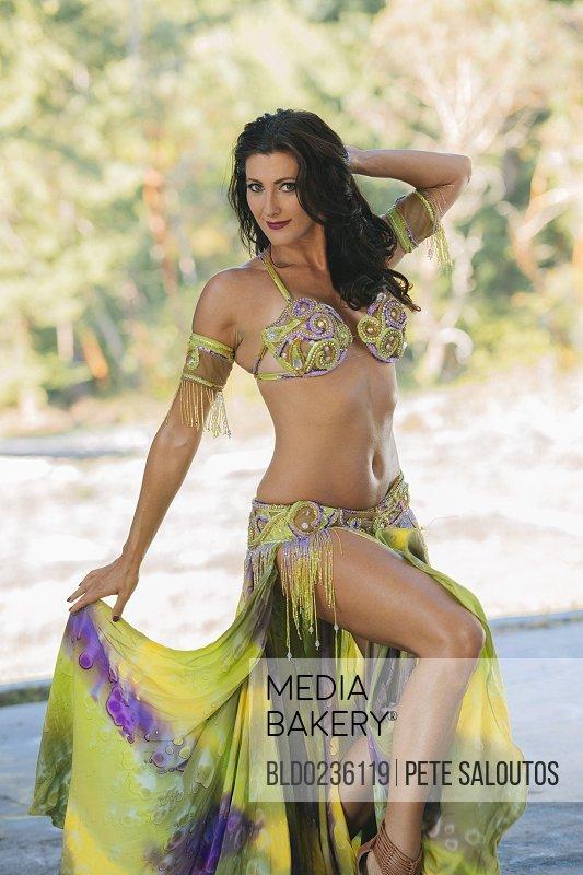 Belly dancer posing holding skirt