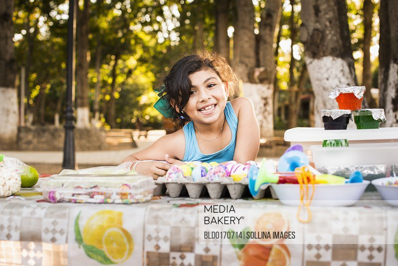 Hispanic girl smiling with Easter eggs