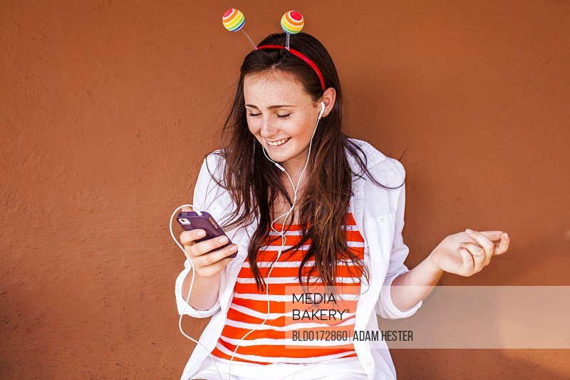 Caucasian woman in novelty antenna listening to mp3 player