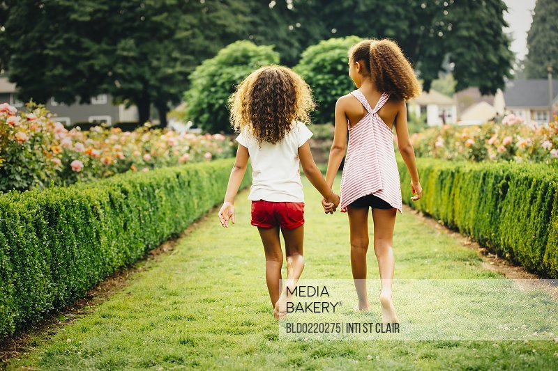 Mixed race sisters walking in garden