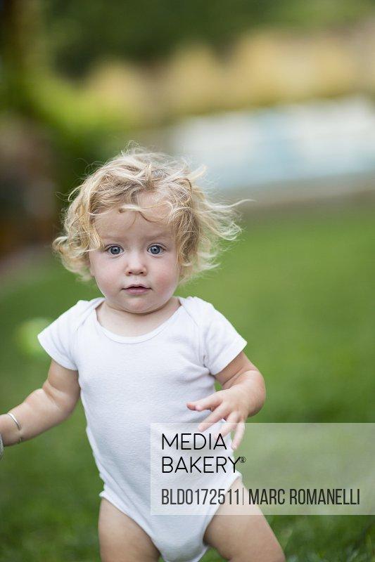 Caucasian baby boy walking in grass