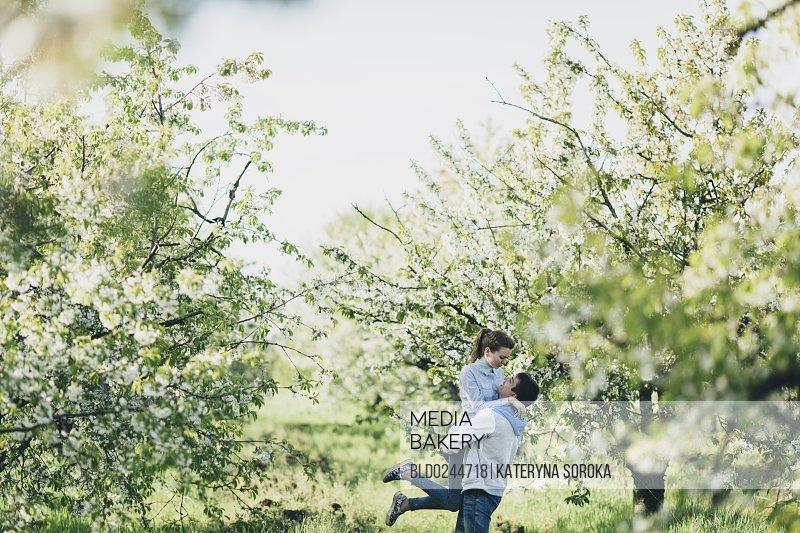 Caucasian man lifting woman under flowering trees