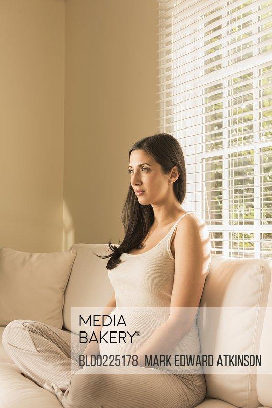 Pregnant Caucasian woman sitting on sofa