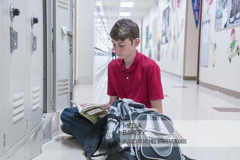 Boy sitting on floor of school corridor reading book
