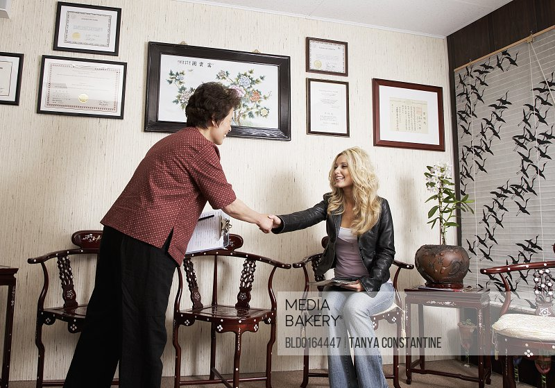Chinese medicine practitioner greeting patient