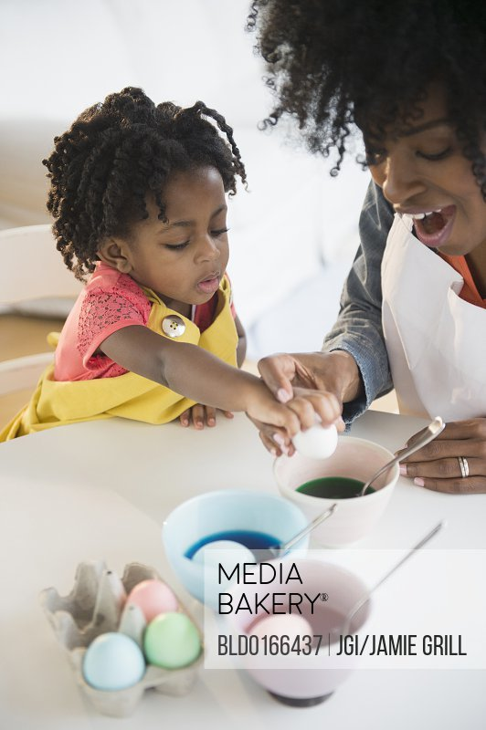 Mother and daughter dyeing Easter eggs