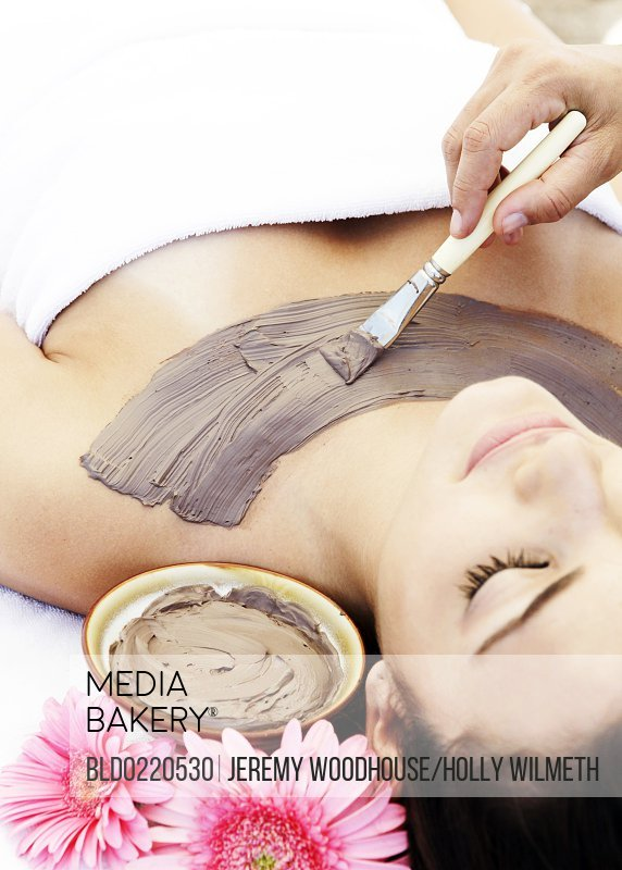 Woman having mud skin treatment in spa