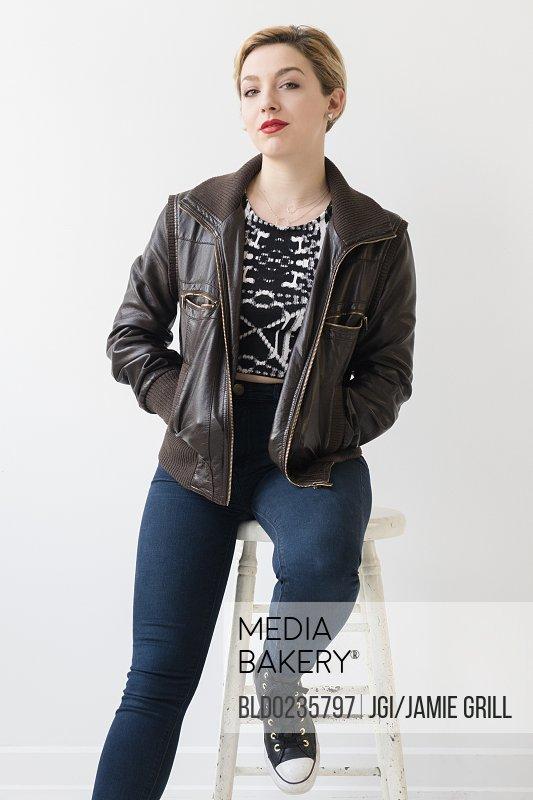 Caucasian woman wearing leather jacket sitting on stool