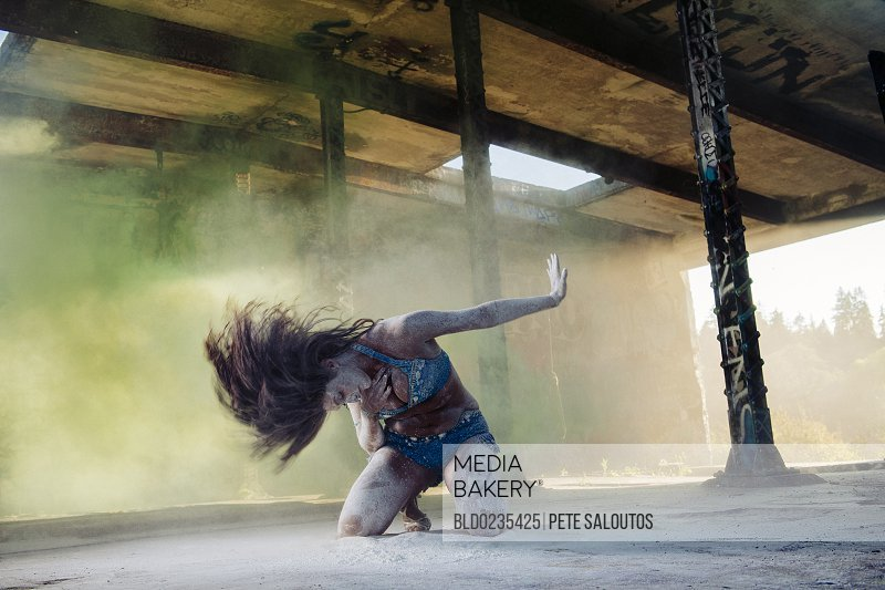 Belly dancer kneeling in powder