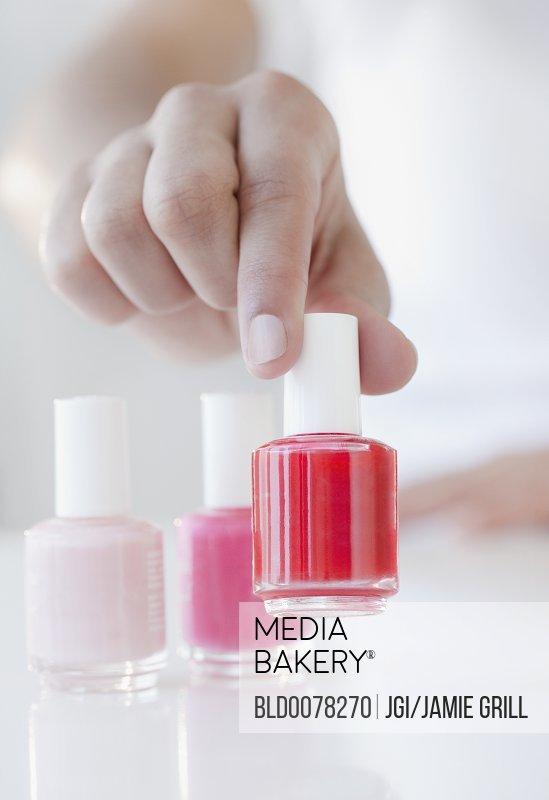 Mediabakery - Photo by Blend Images - Woman choosing red fingernail ...