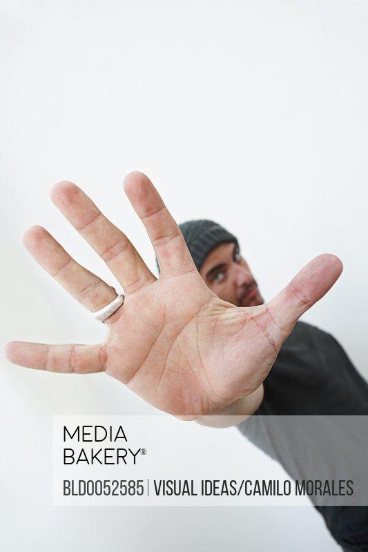 Hispanic man making stop gesture