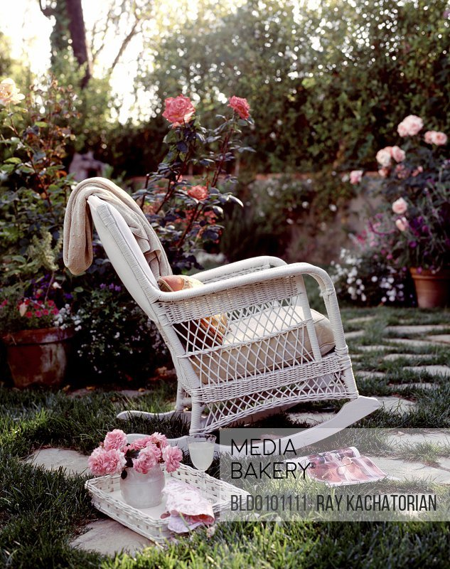 Rocking chair and drinks in blooming garden