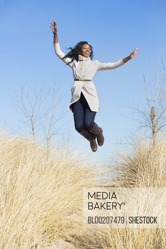 Woman jumping for joy in beach grass