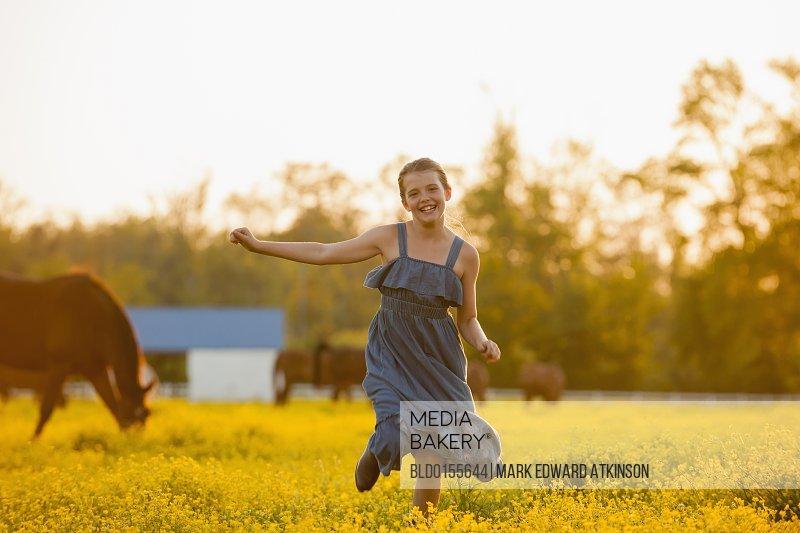 Caucasian girl running in field of flowers