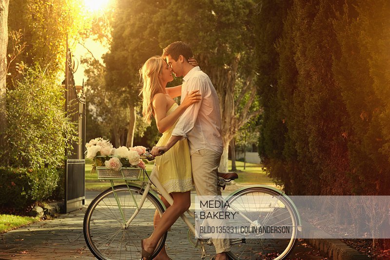 Caucasian couple kissing on bicycle/n
