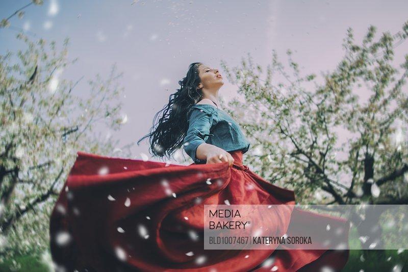 Caucasian woman dancing near flowering trees