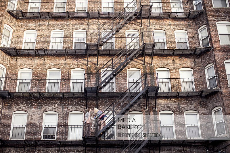Caucasian Standing On Apartment Fire Escape