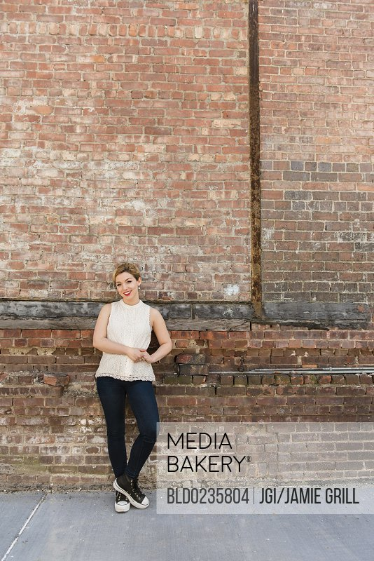 Caucasian woman leaning on brick wall