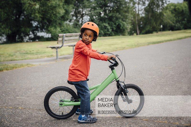 Black boy wearing helmet sitting on bicycle