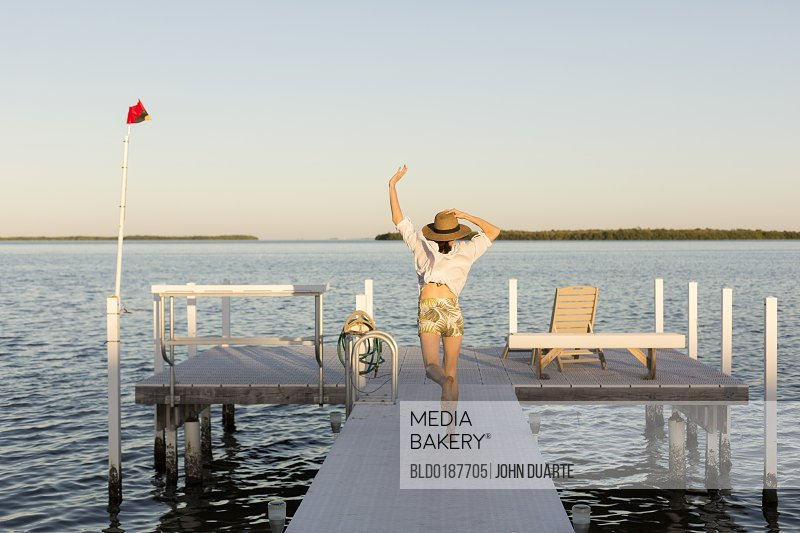 Caucasian woman jumping for joy on pier