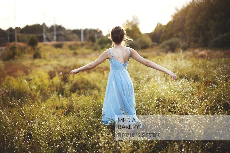 Girl walking with arms outstretched in rural field