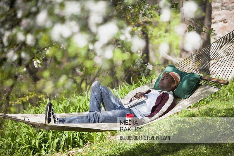 Black man laying in hammock