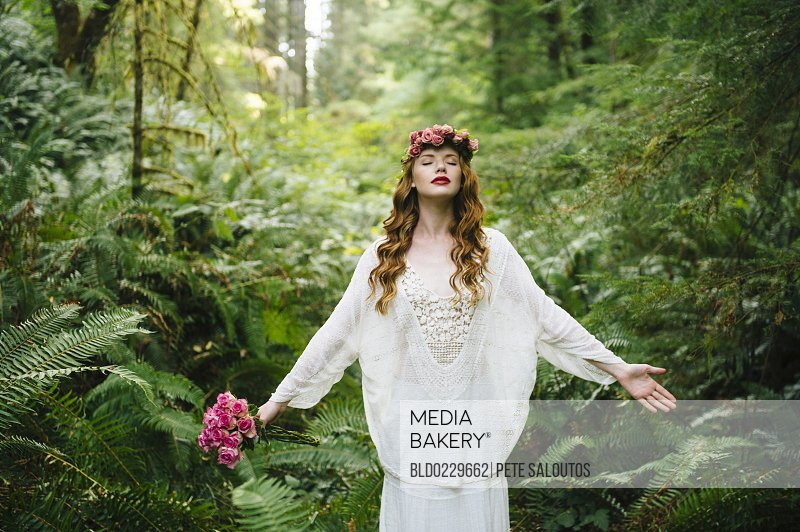 Caucasian woman wearing flower crown in forest