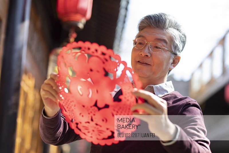 Happy senior man with Chinese New Year paper-cut