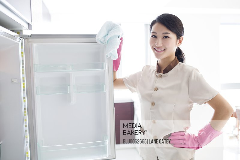 Domestic staff cleaning refrigerator