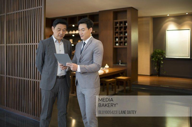 Cheerful businessmen using digital tablet