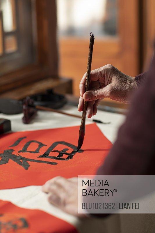 Senior man writing calligraphy on couplets