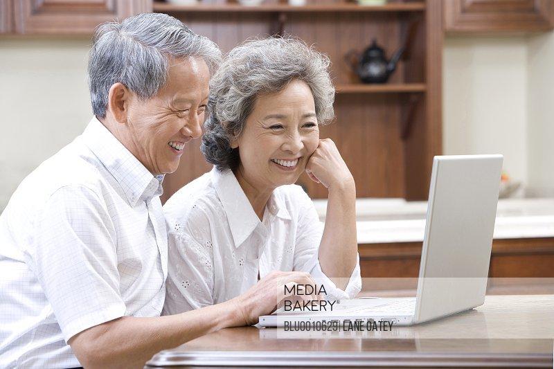 Senior adults using laptop