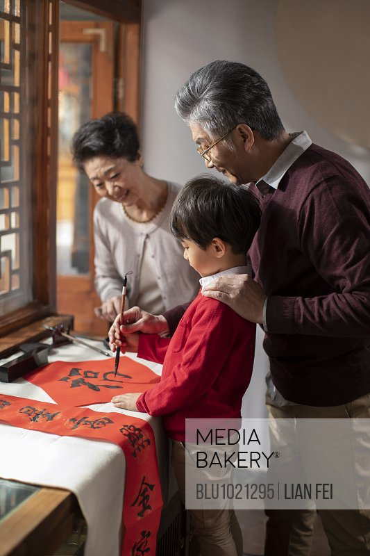 Happy family writing calligraphy on couplets