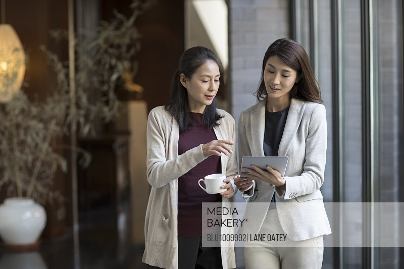 Elegance mature woman talking with young businesswoman