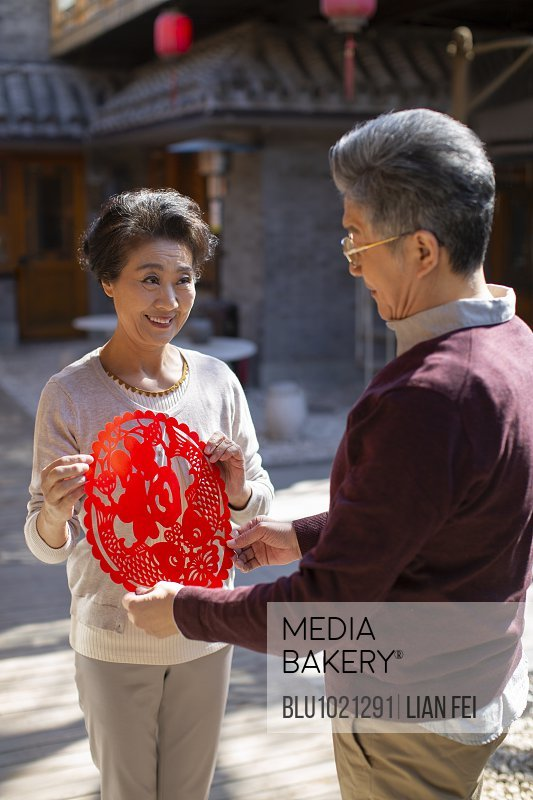 Happy senior couple with Chinese New Year paper-cut