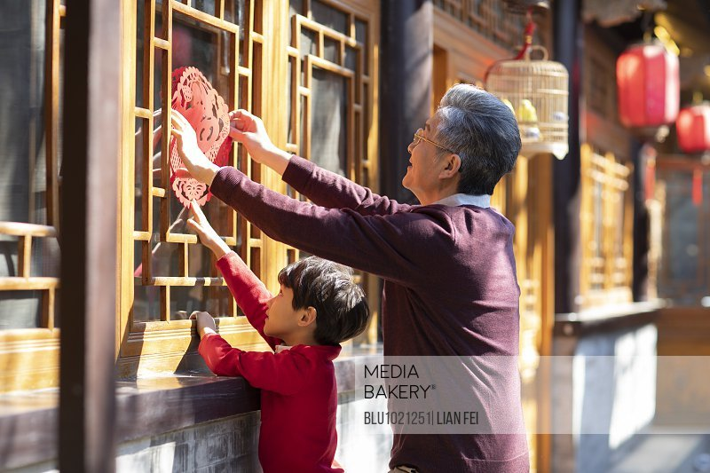Happy grandfather and grandson with Chinese New Year paper-cut in yard