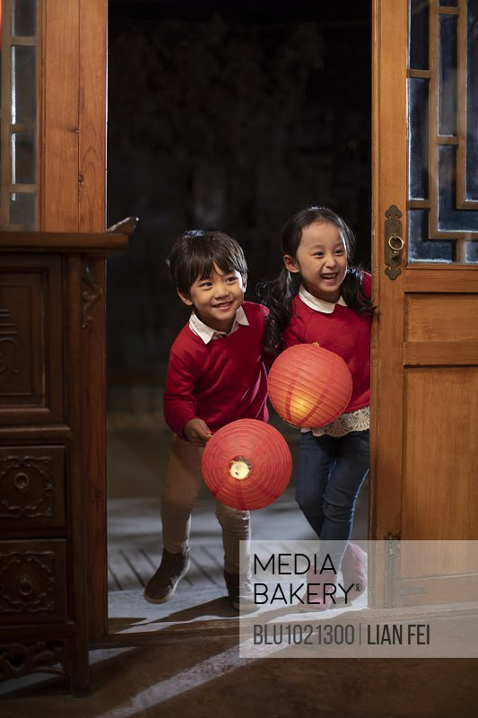 Happy sibling holding Chinese lanterns