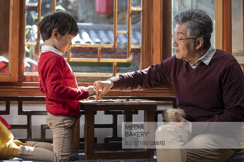 Happy grandfather and grandson playing the game of go