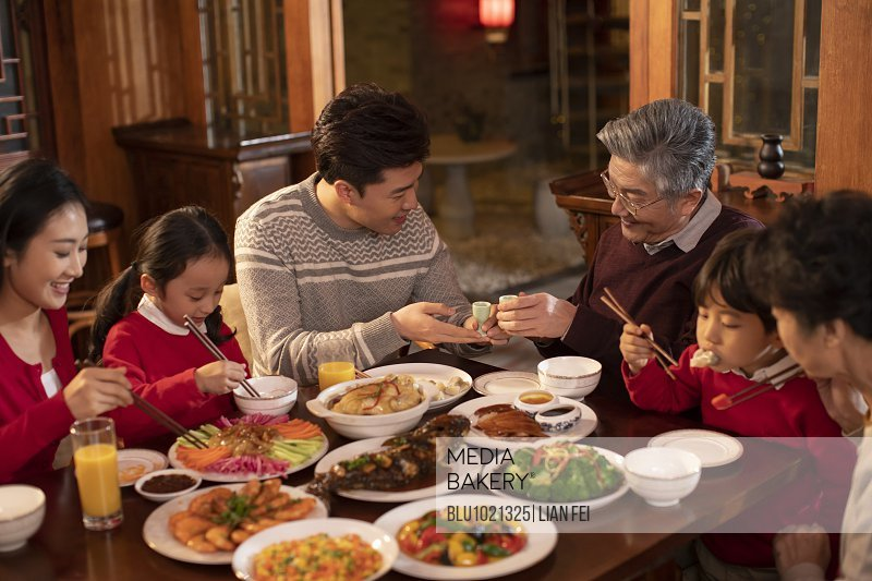 Happy family eating dinner for Chinese New Year