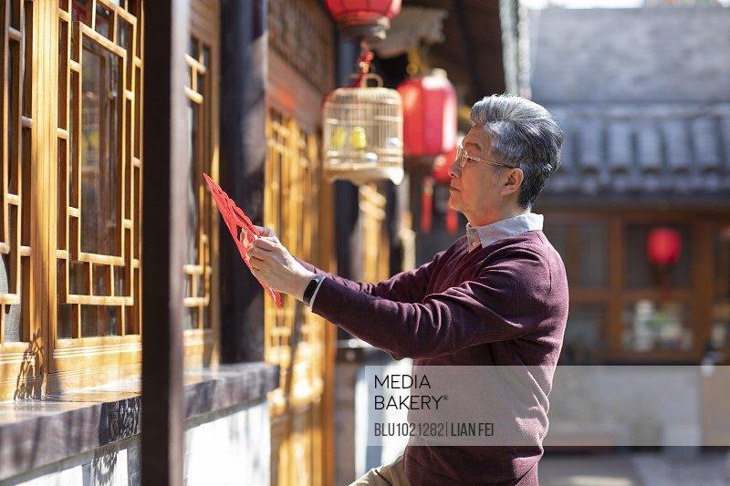 Senior man with Chinese New Year paper-cut